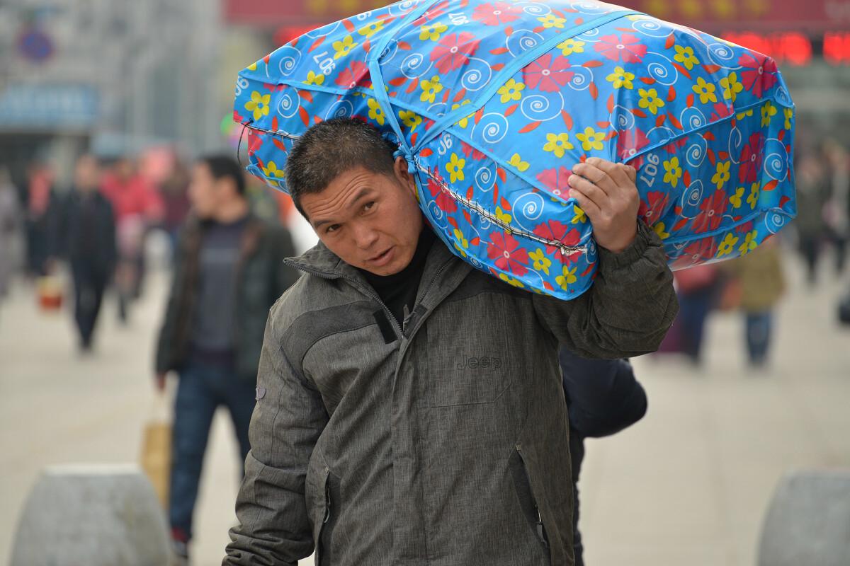 2015年2月7日,安徽蚌埠火车站,在外务工的返乡农民工扛着满满当当的
