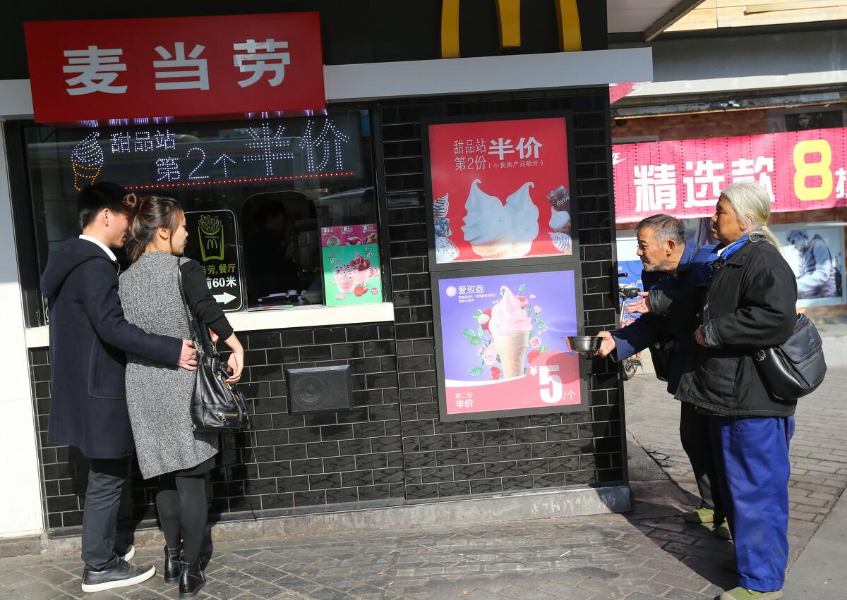 2017年2月13日,在浙江温州街头,一夫妻乞丐向一小情侣伸手行