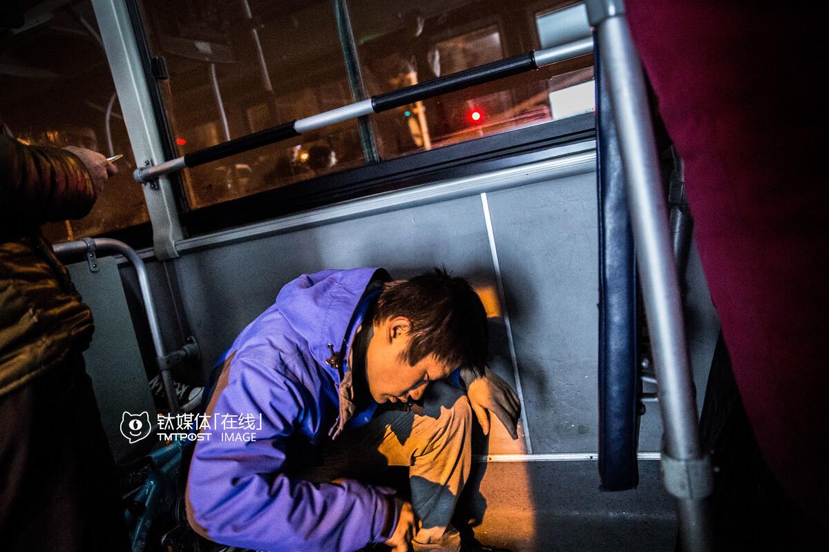 3月19日凌晨1:37,北京,夜班公交上,一名代驾司机坐在折叠车上睡着了。