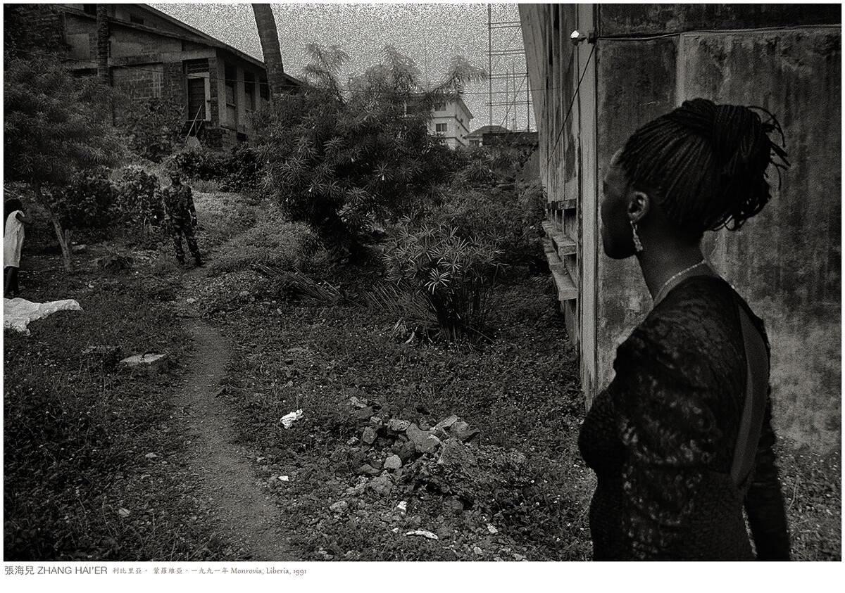 急切等待心上人的阿兵哥,遠遠看見姑娘身邊的攝影師而躊躇不前。利比里亞,蒙羅維亞,一九九一年
