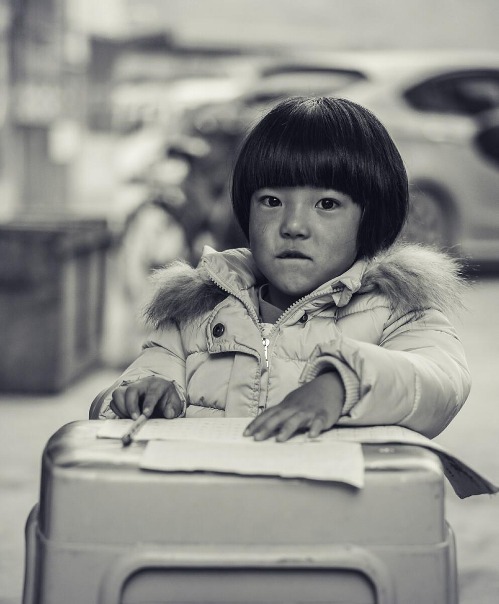 陪着妈妈一起在街边卖烧饼为生的小姑娘,眼中充满渴望知识的