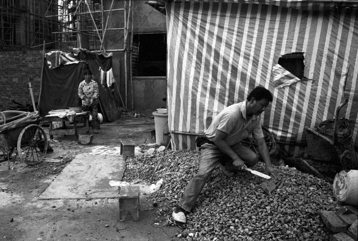 建筑工人一大早磨砖刀,后面是他的临时住所