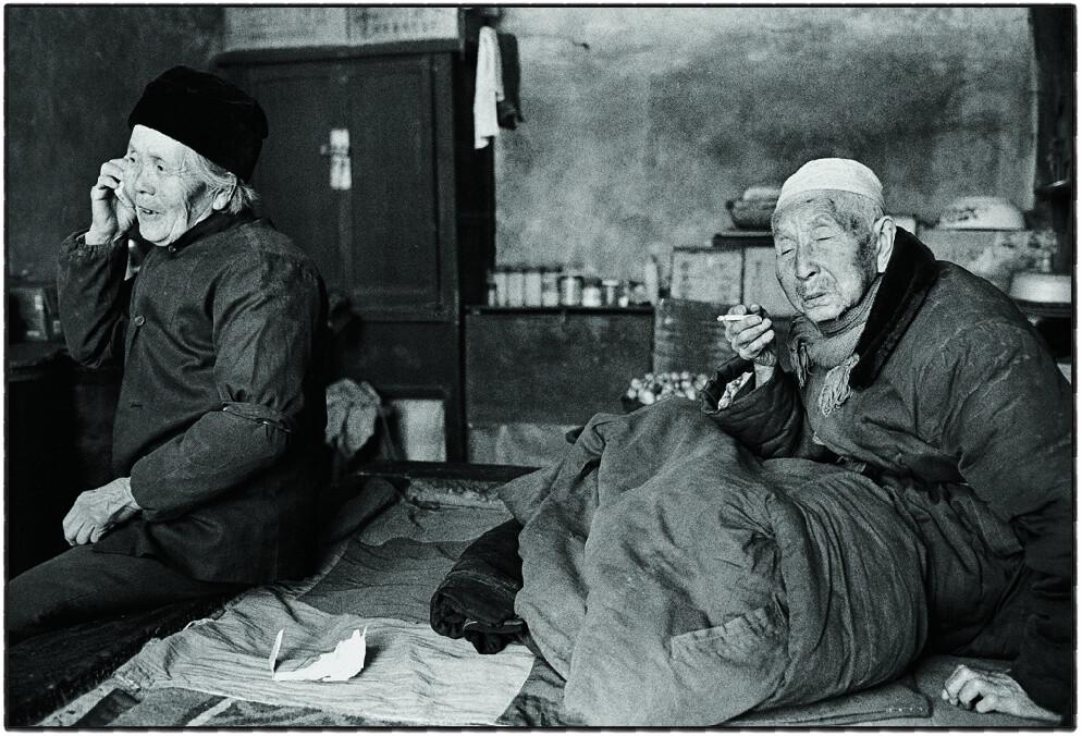 """11、王国安,81岁,住在高高的城墙边上,老伴身体不太好,时不时的被孩子们接到外面去住,他不愿意给孩子添麻烦,坚持一个人住在古城里,每次见到我来,王国安总是热情的邀请到他的小屋中坐一坐,说:""""尽管房子黑,但热水常有,喝点水,暖暖身子""""。(摄于2002年).jpg_(001)"""