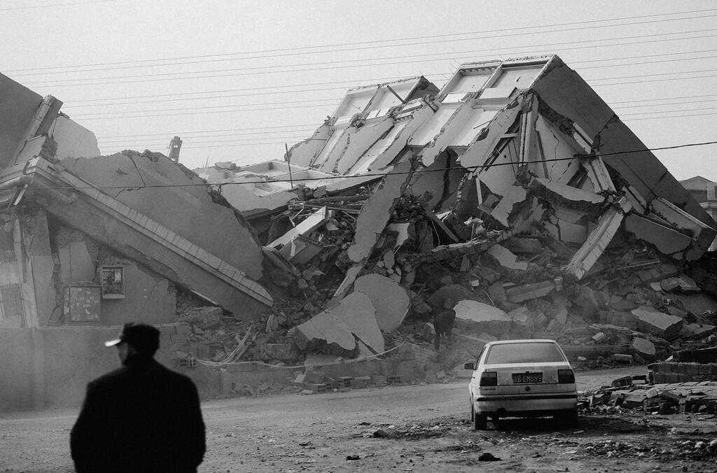 07拆迁户站在扒掉的废墟前看着曾经居住过的房屋。