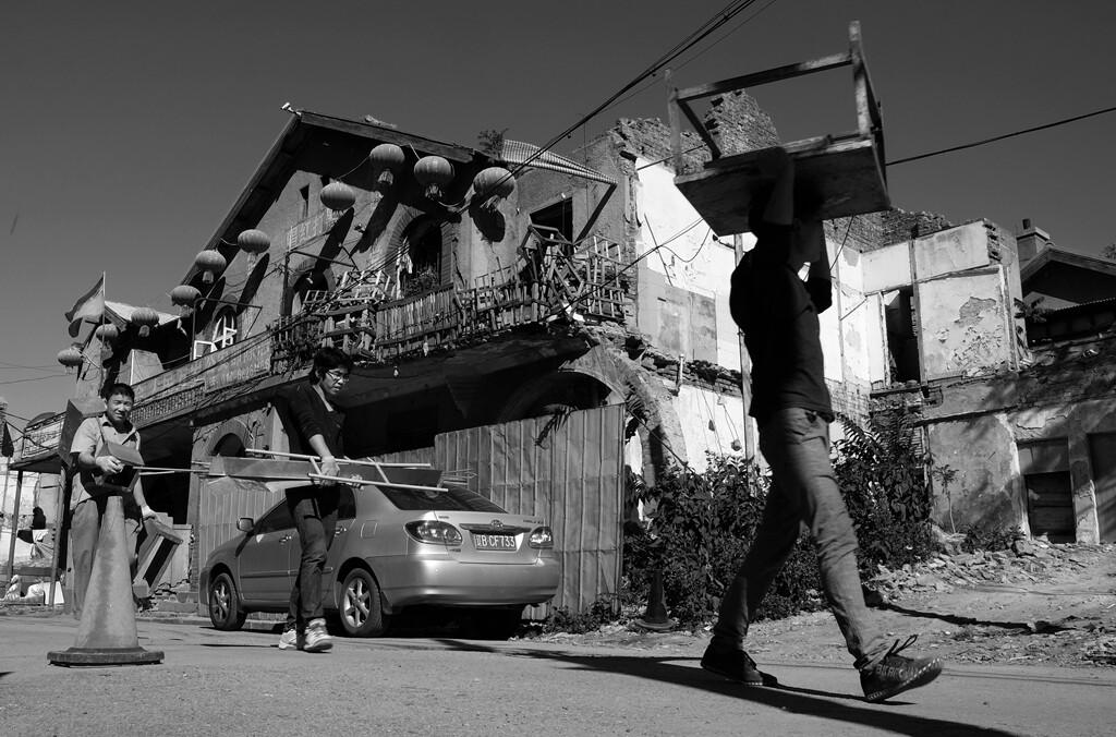 08几名拆迁户扛着简陋的家具正在离开这片曾经的家园。