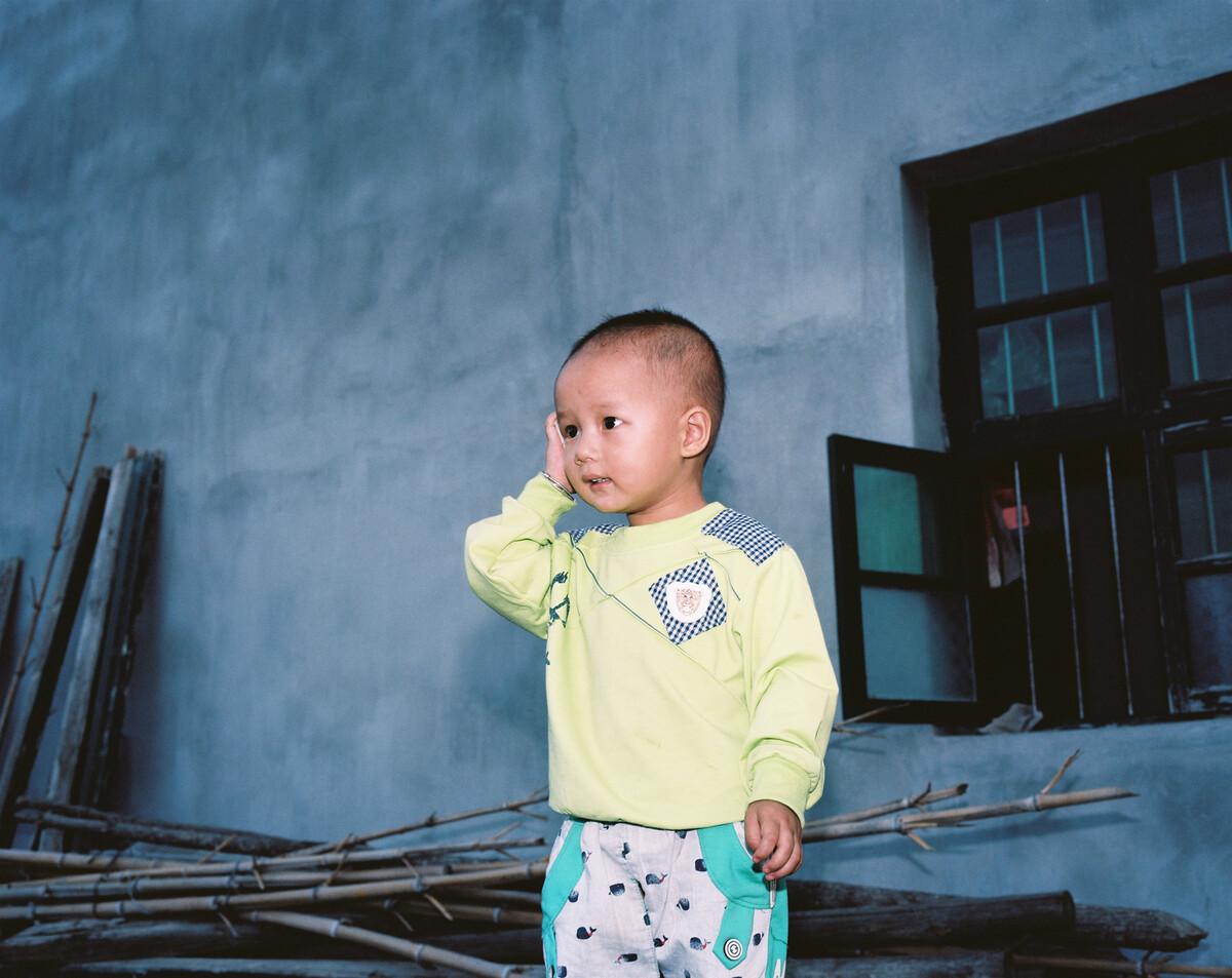 2014年,四岁的罗竞拿着石头给在外打工的妈妈打电话。Mamiya 7II + 85/4,柯达120负片。