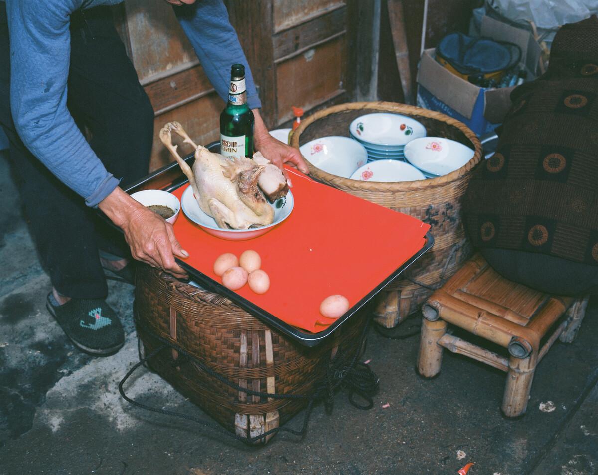 2014年,村民在操办孩子满月酒时祭祖。Mamiya 7II + 85/4,柯达120负片。