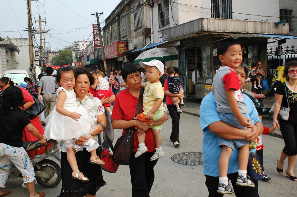2008年9月3日,无锡振兴路,接幼儿园小朋友放学,一人抱一个宝贝。在独生子女时代,一个孩子6个人疼爱。年轻的父母上班比较忙,接送孩子的任务就落在老人身上。