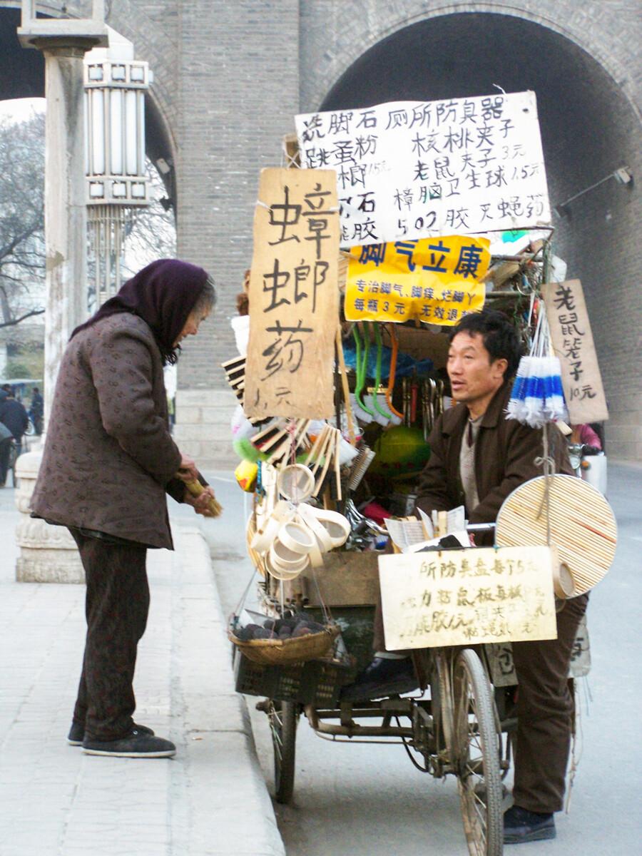 2005年12月24日,西安城墙下,一位老人与流动小贩在聊天。