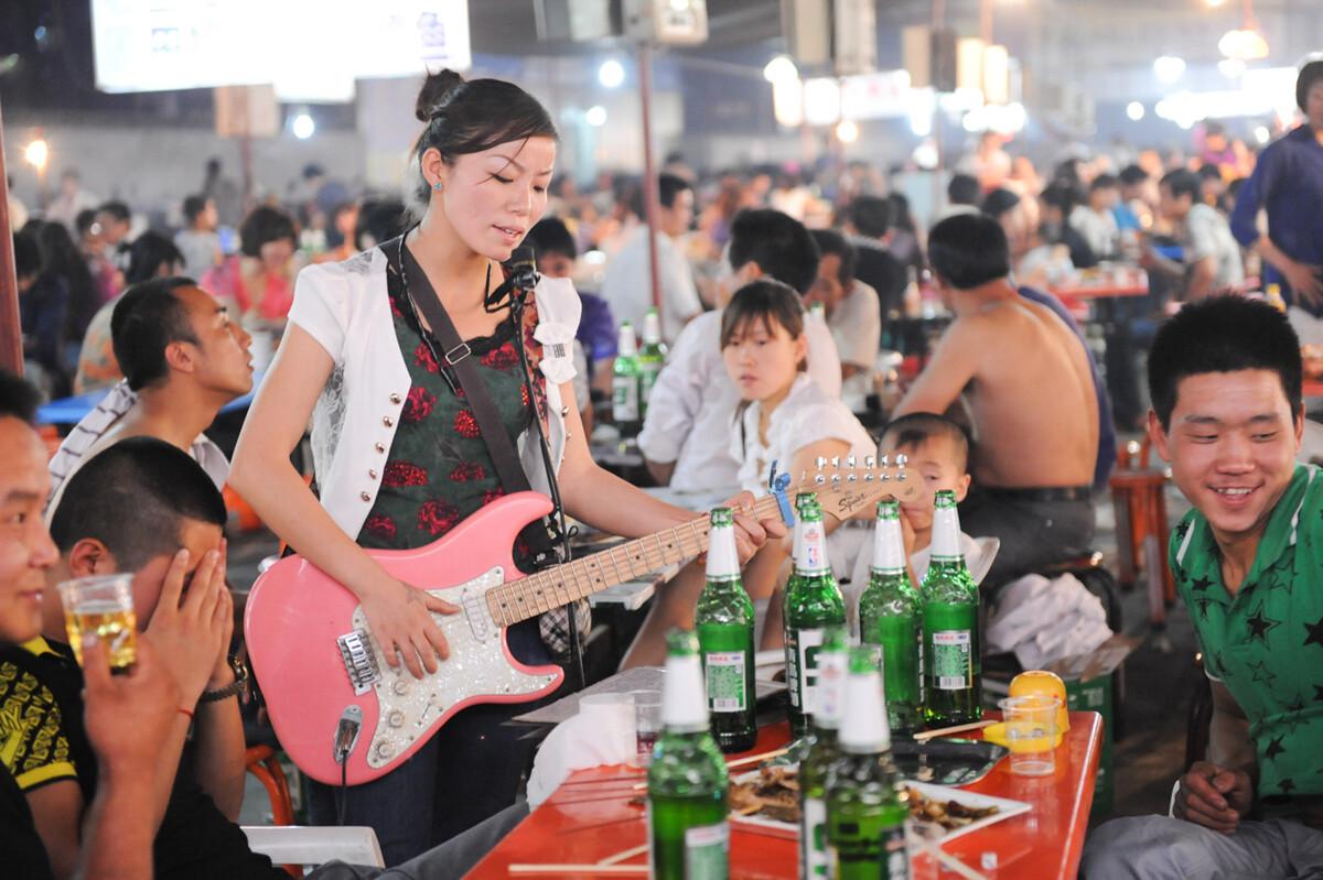 2011年6月10日,陕西韩城,夜宵大排档里卖唱的姑娘。