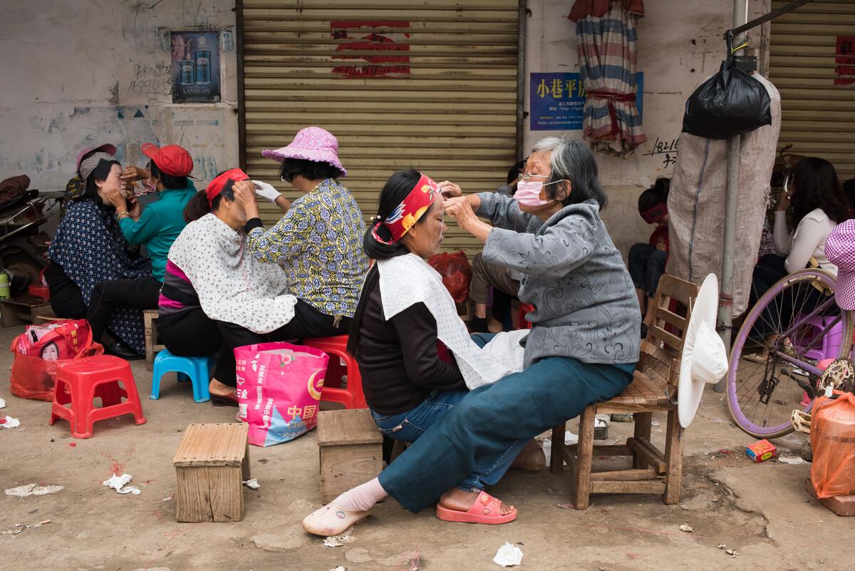 2020年1月22日(农历廿八),湛江徐闻,妇女们在市井里进行传统的拉脸毛,准备迎接农历新年的到来。