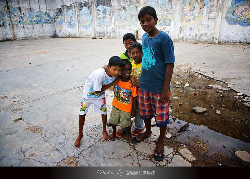 2012年2月7日 斯里兰卡 科伦坡<br /> 斑驳的墙壁依稀可见卡通图案,几个踢足球的男孩子好奇的凑过来,面对镜头羞涩又好奇