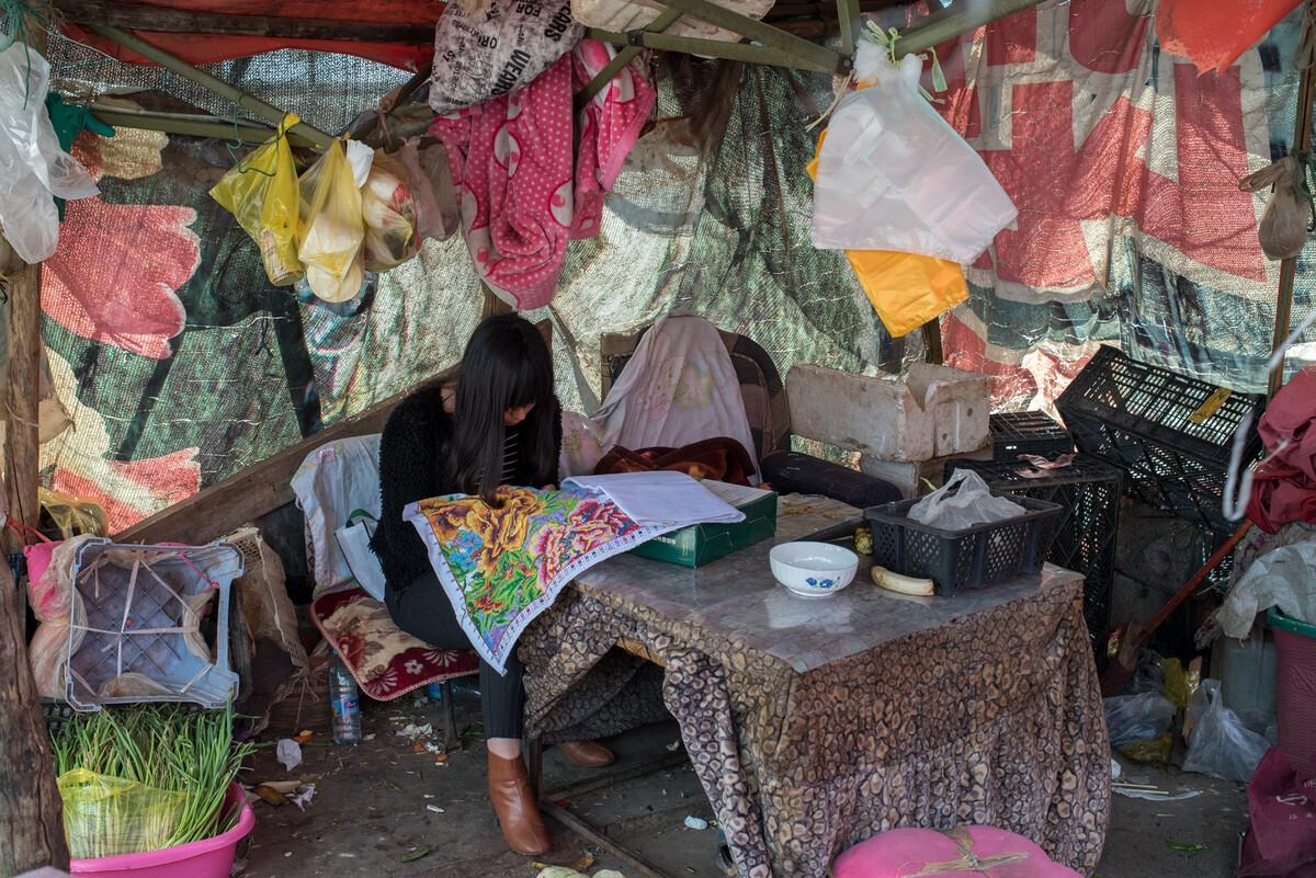 2019年2月28日云南鲁甸县,一临时搭建的摊位里,妇女在秀十字绣。