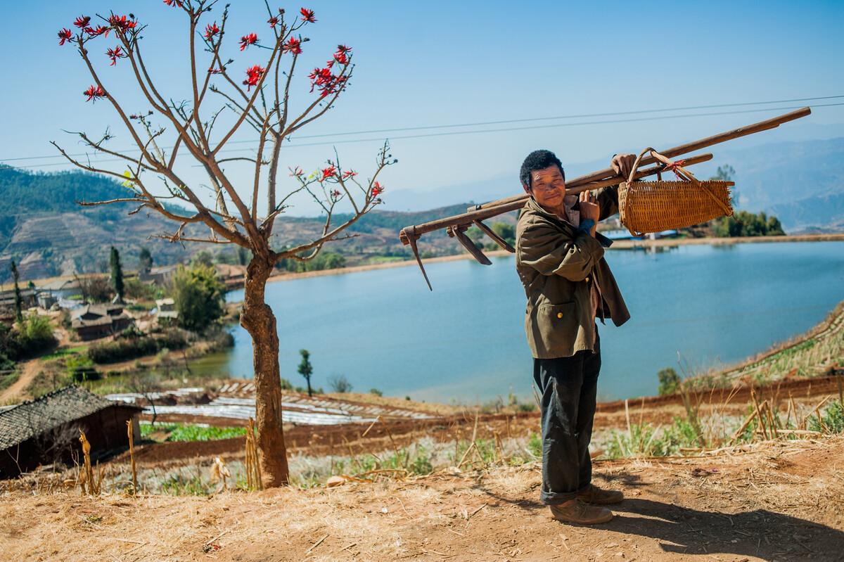 2013年2月20日四川米易县新山傈僳族乡,准备去田里务农的农民。