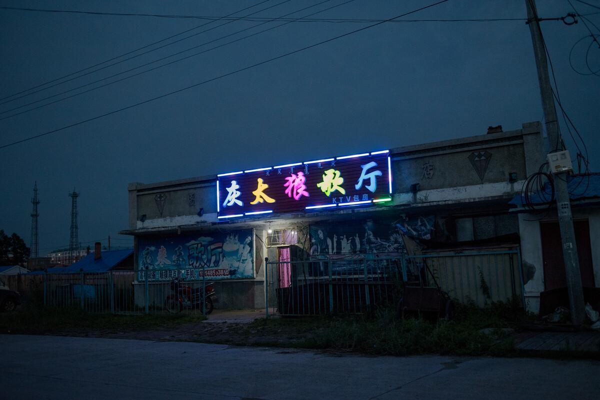 2018年7月23日内蒙古牙克石市图里河镇,夜幕之下营业的歌厅泛着点光亮,大兴安岭禁止伐木后,因林而兴的小镇开始衰退。