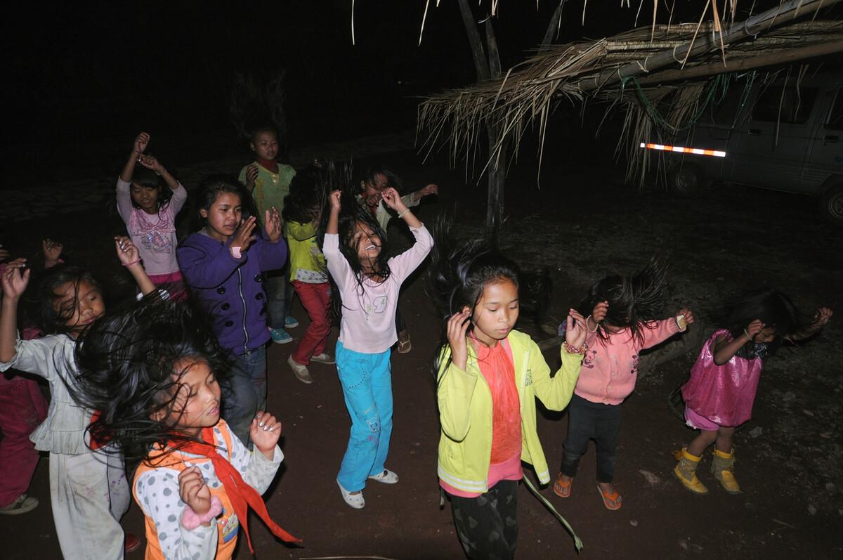 """2010年4月2日云南沧源县勐角乡翁丁村,晚上村里的小女孩在《阿佤人民唱新歌》伴奏下练习""""甩发舞""""。"""