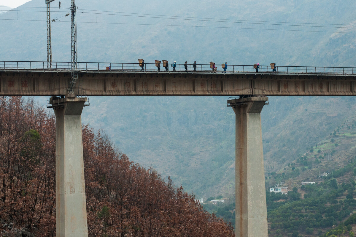 2014年2月22日贵州水城县营盘乡,当地人走过北盘江铁路大桥。
