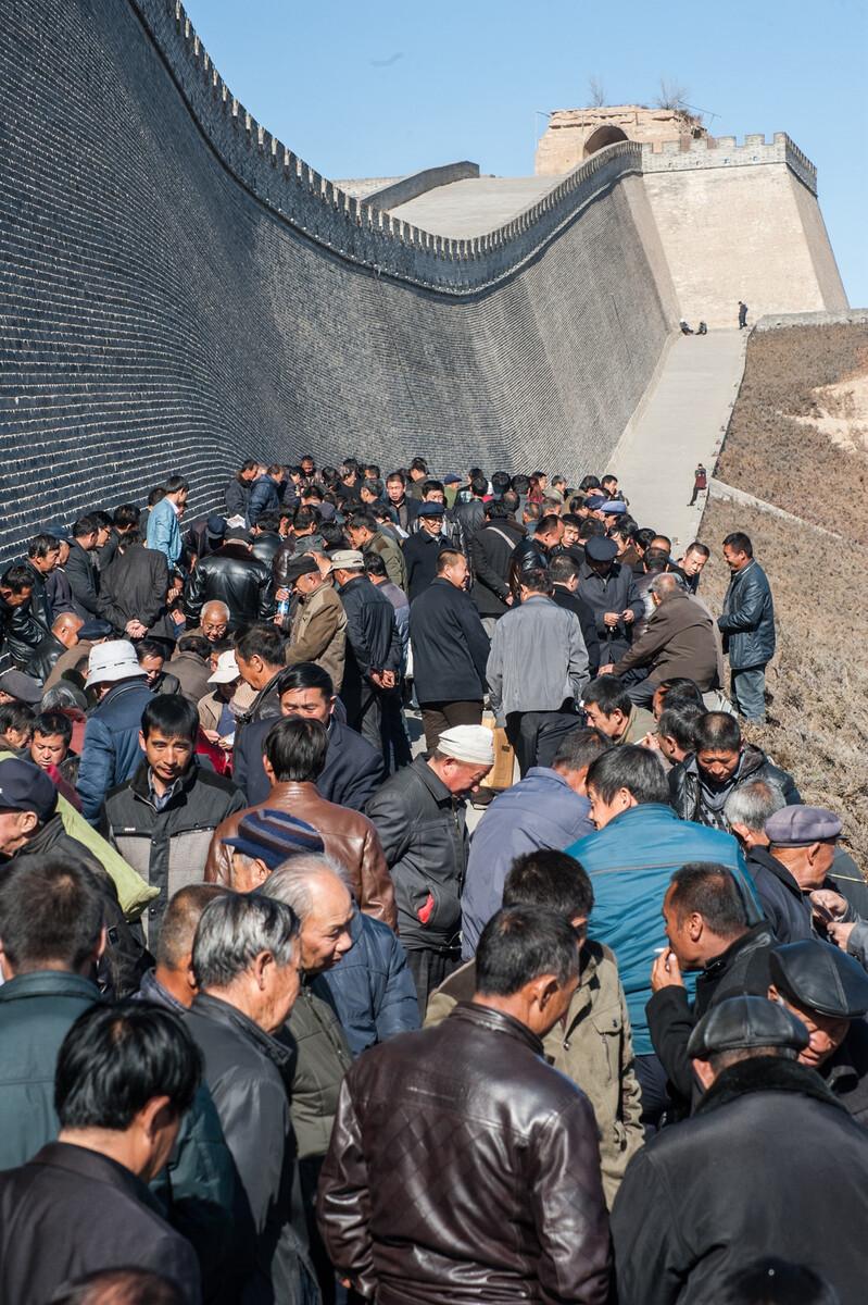 2015年3月9日陕西榆林,当地人在新维修的城墙下聊天打牌下棋娱乐。