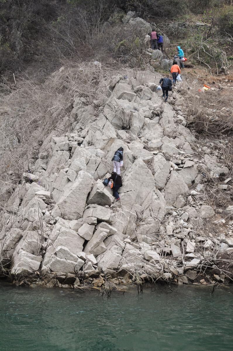 2011年3月19日重庆巫山至培石的班船停靠沿途一处码头后,当地人爬过岸边的石坡才能走上回家的小道。