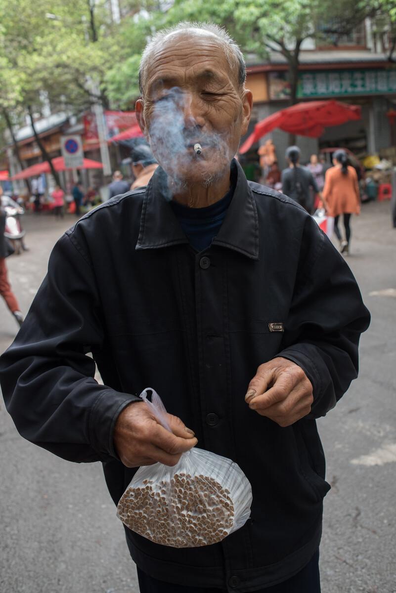 2019年4月23日湖南麻阳县老人买了一袋私家自制的卷烟并点上一支,自制的卷烟论斤卖,10元一斤。