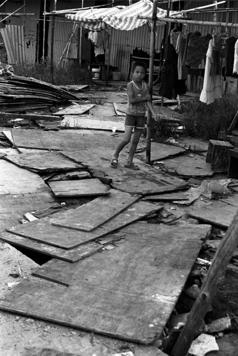一个小孩在民工的临时住所前玩耍。而一周后民工全部迁走