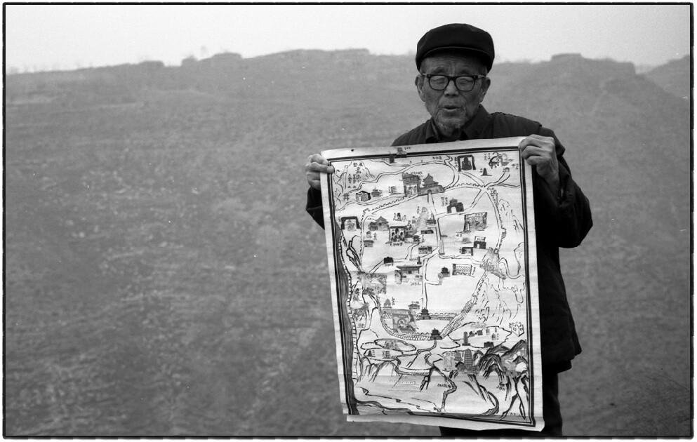 5、王春育、今年81岁,被誉为古城活字典,人们说他是古城的宝贝。他用香烟盒上的图案粘贴制作了这张古城全貌图。.jpg