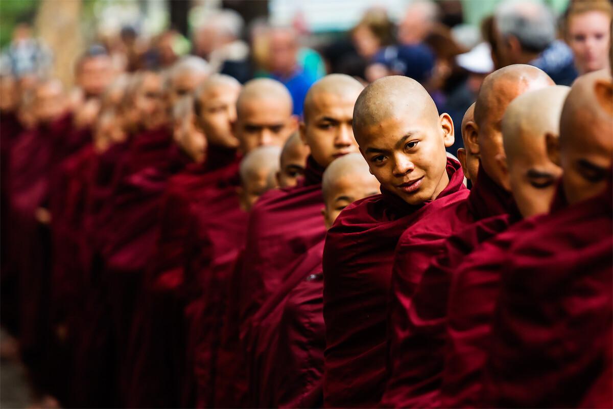 """在马达哈根杨僧院,僧侣们谨遵""""过午不食""""的佛规,中午12点前化缘回来后,排成长队,托钵进入院内餐厅共同进食。排队时要求目光保持在前方三英尺,不可左顾右盼,但我还是在僧群中发现了这个小僧侣将头探了出来,略带微笑的看着围观人群。"""