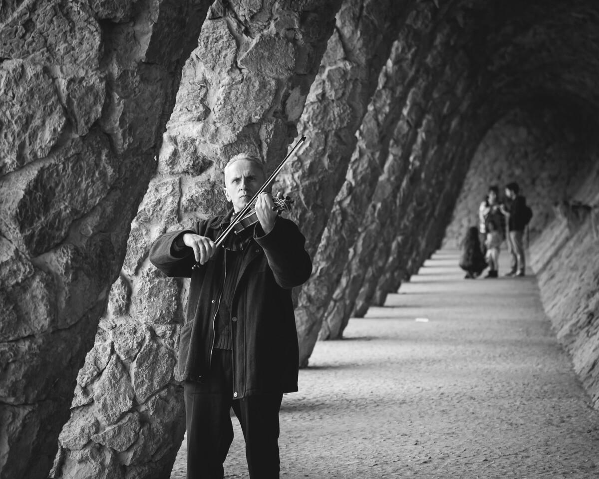 """古埃尔公园是高迪建筑的另一个大观园,图中的老人正独自在""""石头走廊""""里拉着小提琴,琴声悠扬,阳光正好。<br /> <a href=""""https://park.tuchong.com/"""" target=""""_blank"""">@Park</a> Güell"""