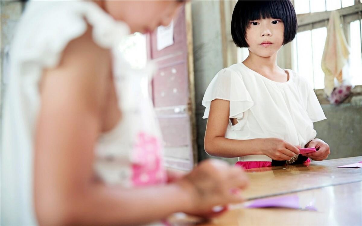 """李丽娟,3年级,父母在广州打工。志愿者小颖教孩子们做手工,叠礼物送给自己最想送的人。李丽娟看着别的小朋友叠好的千纸鹤,眼神中满是羡慕。她其实也想叠好送给自己的爸爸妈妈,可是,离爸爸妈妈回来还有好几个月呢!李丽娟也很喜欢吹口琴,她说:""""我要把口琴练好,等到过年妈妈回来的时候就吹给她听,给她一个惊喜!"""""""