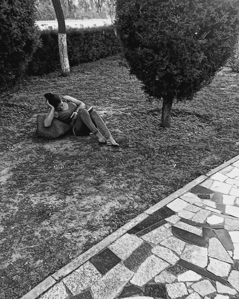 偶过公园,遇一女子坐屐靠石玩手机。