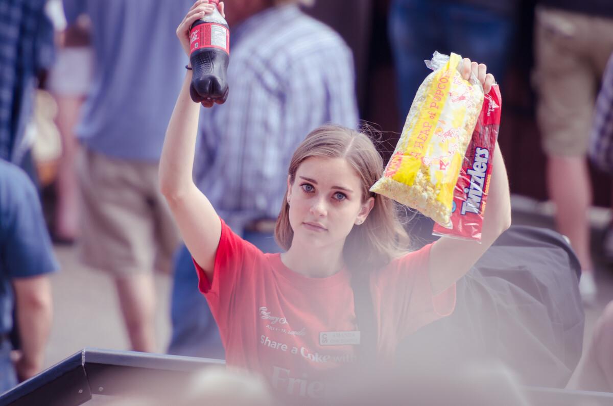 在牛仔竞技主会场叫卖食品的志愿者们。即使你在观看比赛前来不及吃饭,也可以一边看比赛一边吃。