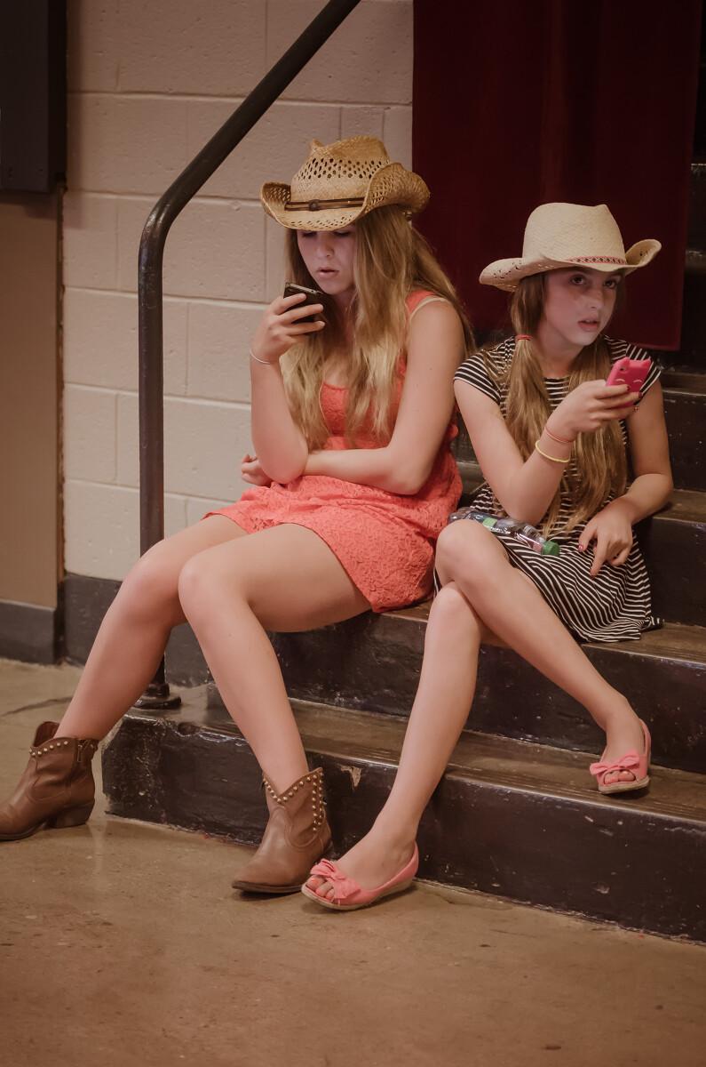 在休息处抓拍的两个低头玩手机的姐妹。
