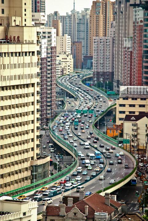 3月影赛建筑风景篇三等奖  曲直<br /> 孙中原(上海) 这是在静安区的一栋大楼里隔着幕墙玻璃拍摄的照片。当天是阴天,所以原本准 备拍摄的是夜景,但下班高峰的提前来临使得高架上拥堵的车辆与两旁高楼密集的窗户呼应起来,这种川流在拥挤中的状态也是上海和现代都市的一种生存现状。