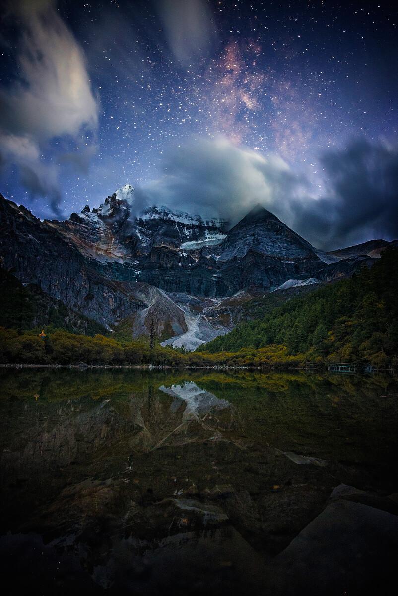 图中的雪山是川西稻城亚丁的三神山之首,海拔6032米的仙乃日。经历了一个乌云遮天的白天后,日落后山顶的天空中奇迹般地出现了无云的窗口,估算了方位后,我们临时决定冒险在珍珠湖畔等待夜幕降临。最后的天文昏影即将消失,山下湖畔艳丽的秋林已经开始隐没于昏暗中,而灿烂的星河已经开始出现在天空中。仙乃日的峰顶依然暗云奔涌,仿佛拒绝以真面目示人。